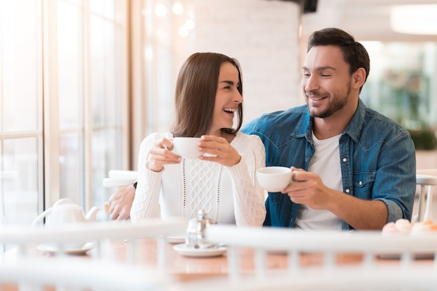 Un couple passe un bon moment au café à raconter des histoires.