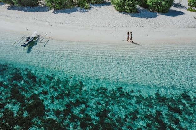 Couple de passer du temps sur une belle île tropicale isolée aux philippines. concept de vacances et de style de vie. vue aérienne