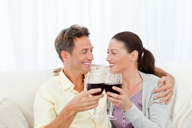 Couple passionné, boire du vin rouge tout en vous relaxant sur le canapé