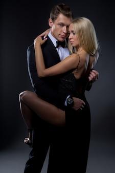 Couple passionné: une femme avec une coiffure légère dans une robe de soirée noire et un bel homme en costume avec un nœud papillon posent dans un studio sombre