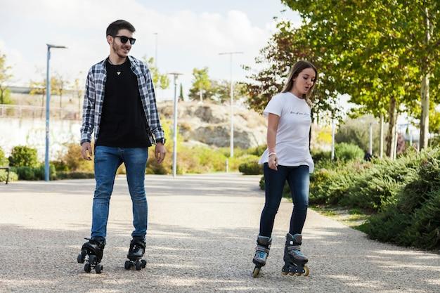 Couple de patinage à roulettes dans le parc