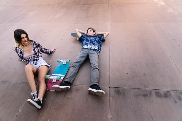 Un couple de patineurs couché dans la demi-pipe