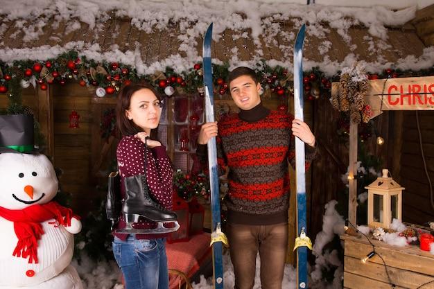 Couple avec patins et skis debout devant la cabane en rondins en hiver