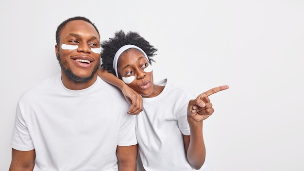 Un couple à la peau foncée en t-shirts décontractés applique des patchs de beauté sous les yeux, regarde au loin, isolé sur un mur blanc, subit des procédures de soins de la peau pose ensemble à l'intérieur. petite amie ethnique