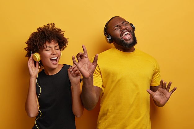Un couple à la peau sombre énergique et énergique danse et s'amuse ensemble, écoutez différents types de musique dans des écouteurs isolés sur fond clair.