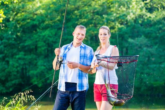 Couple de pêche sportive se vanter avec des poissons pêchés