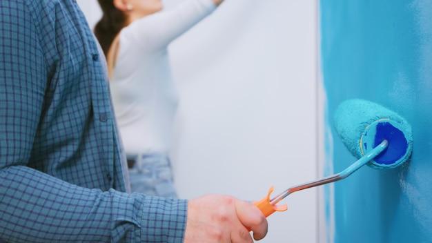 Couple peignant le mur ensemble tout en redécorant la maison. redécoration d'appartements et construction de maisons tout en rénovant et en améliorant. réparation et décoration.