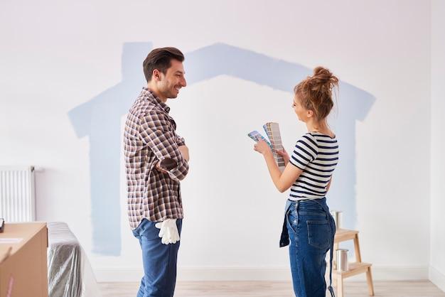 Couple peignant le mur intérieur dans leur nouvel appartement