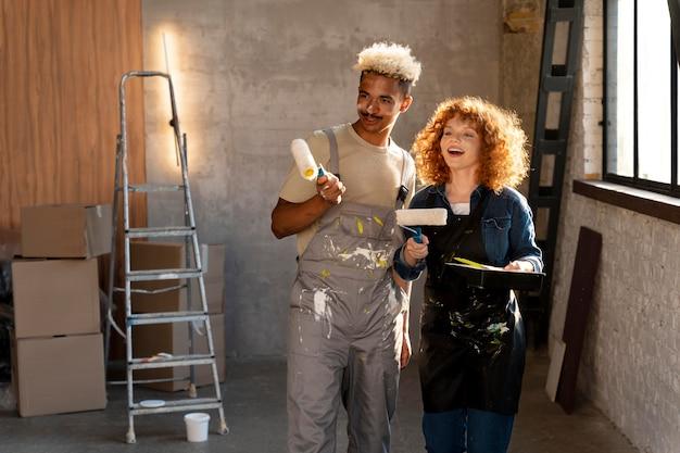Couple peignant les murs de leur nouvelle maison ensemble