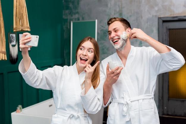 Couple en peignoirs prenant un selfie
