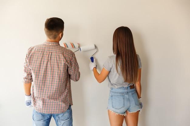 Couple de peintres peignant un mur avec un rouleau à peinture