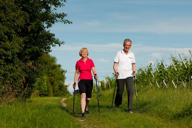 Couple de personnes âgées actives faisant de la marche nordique