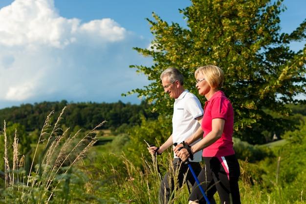 Couple de personnes âgées actives en randonnée avec des bâtons de marche nordique