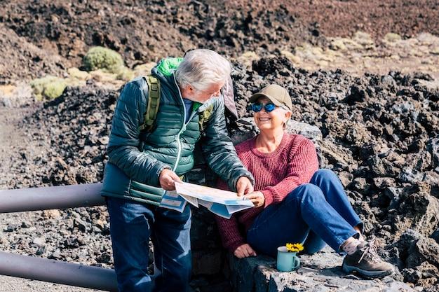 Couple de personnes âgées actives en randonnée et vacances de voyage activité de loisirs en plein air ensemble à la recherche d'une carte papier pour planifier le voyage - les personnes âgées s'amusent avec l'activité sportive dans la nature montagne - jeune