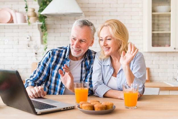 Couple de personnes âgées agitant leurs mains lors d'un appel vidéo en ligne sur un ordinateur portable