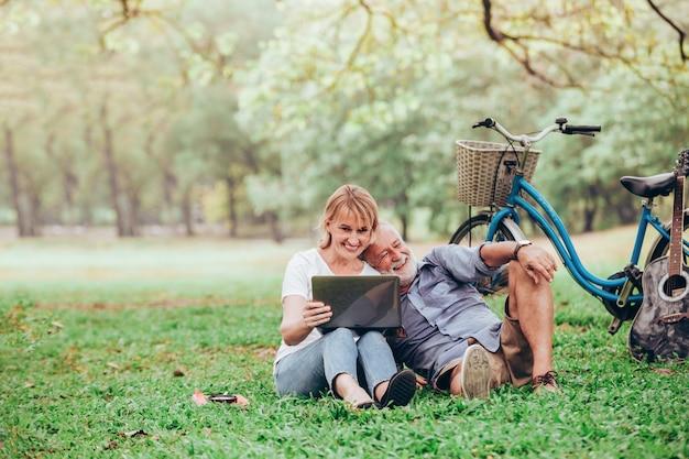 Couple de personnes âgées à l'aide d'un ordinateur portable tout en étant assis sur l'herbe dans le parc
