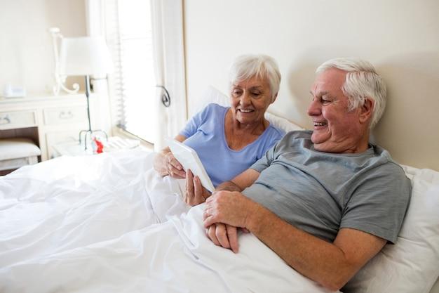Couple de personnes âgées à l'aide de tablette numérique dans la chambre à la maison