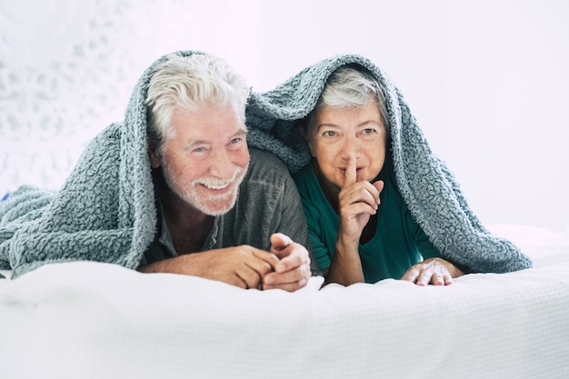 Couple de personnes âgées allongé sur le devant et faisant des gestes du doigt sur les lèvres du lit. couple de personnes âgées passant des loisirs ensemble. heureux vieux couple allongé sur un lit confortable recouvert d'une couverture avec le doigt sur les lèvres