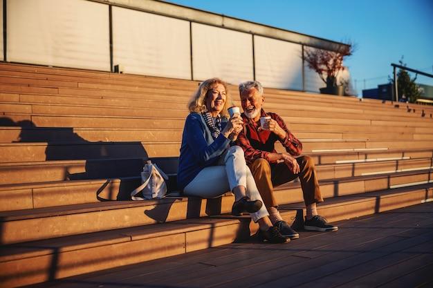 Couple de personnes âgées amoureux assis à l'extérieur sur les escaliers et boire du café à emporter.