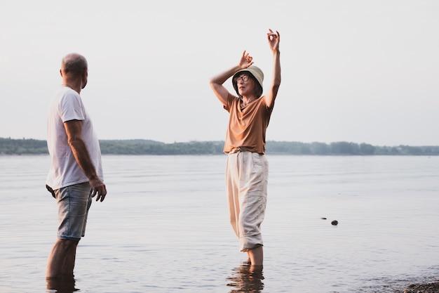 Couple de personnes âgées amoureux dansant et marchant au bord de la mer ou de la rivière au coucher du soleil d'été