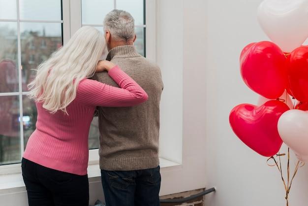Couple de personnes âgées à angle élevé regardant sur fenêtre