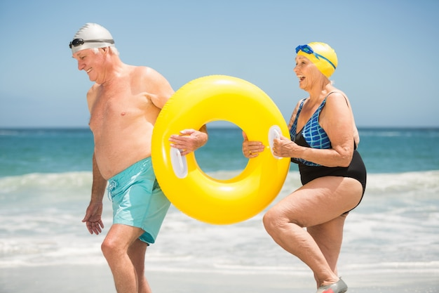 Couple de personnes âgées avec anneau de natation à la plage