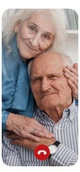 Couple de personnes âgées appelant quelqu'un par appel vidéo