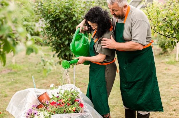 Couple de personnes âgées arroser des fleurs