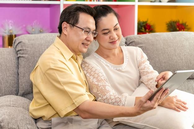 Couple de personnes âgées asiatique à la retraite à la recherche de tablette en maison de soins infirmiers