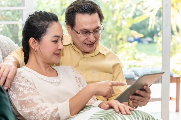 Couple de personnes âgées asiatique à la retraite à la recherche de tablette en maison de soins infirmiers.