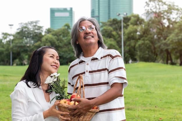 Couple de personnes âgées asiatiques avec bonheur de style de vie panier de fruits dans le parc.