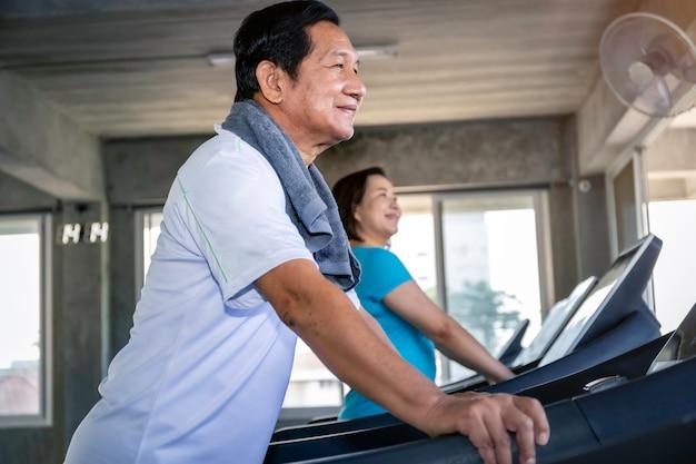 Couple de personnes âgées asiatiques souriant dans des vêtements de sport exerçant au gymnase.