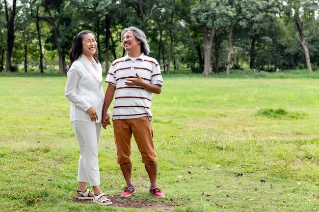 Couple de personnes âgées asiatiques souriant et marchant dans le parc.