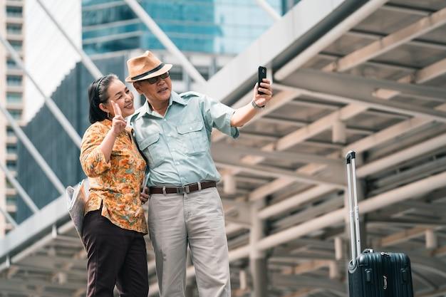 Couple de personnes âgées asiatiques touristes visitant la capitale, tenant un téléphone mobile prendre une photo et un selfie avec plaisir et plaisir