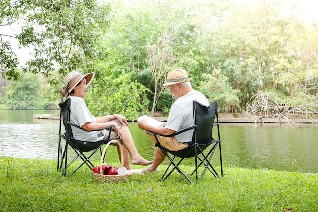 Couple de personnes âgées assis sur des chaises près du lac