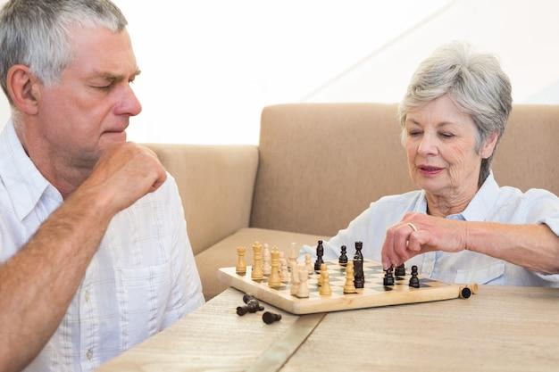 Couple de personnes âgées assis sur le sol jouant aux échecs