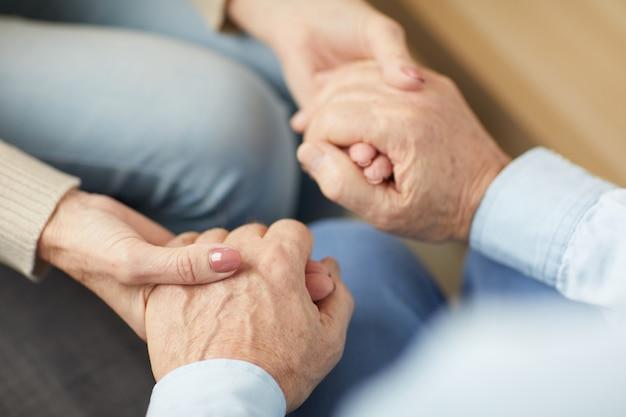Couple de personnes âgées attentionné, main dans la main