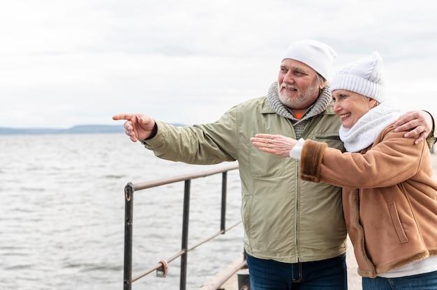 Couple de personnes âgées au bord de mer pointant ensemble