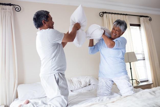 Couple de personnes âgées ayant une bataille d'oreillers