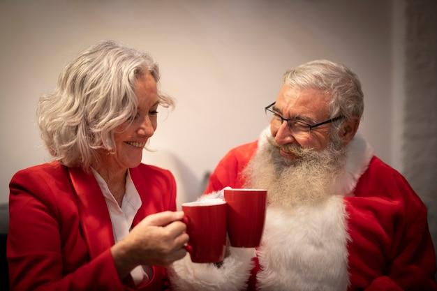 Couple de personnes âgées ayant des boissons de noël