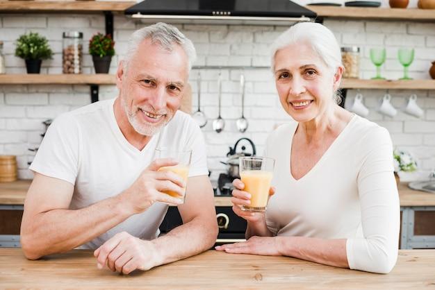 Couple de personnes âgées ayant un jus