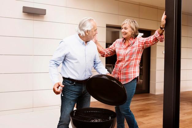 Couple de personnes âgées avec barbecue