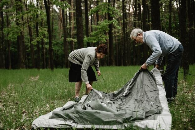 Couple de personnes âgées bénéficiant de vacances et installe la tente. les adultes passent leurs vacances d'été dans la nature et plantent une tente. les aînés campent et assemblent la tente