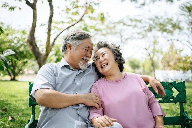 Couple de personnes âgées en bonne santé sièges relaxants sur le banc dans le parc