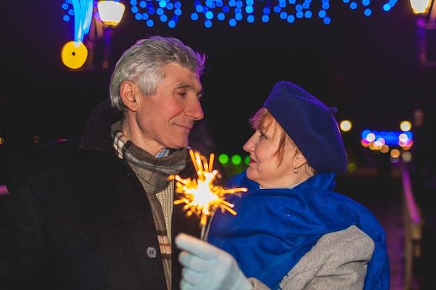 Couple de personnes âgées brûlant des cierges magiques par l'éclairage de vacances la nuit noël et nouvel an