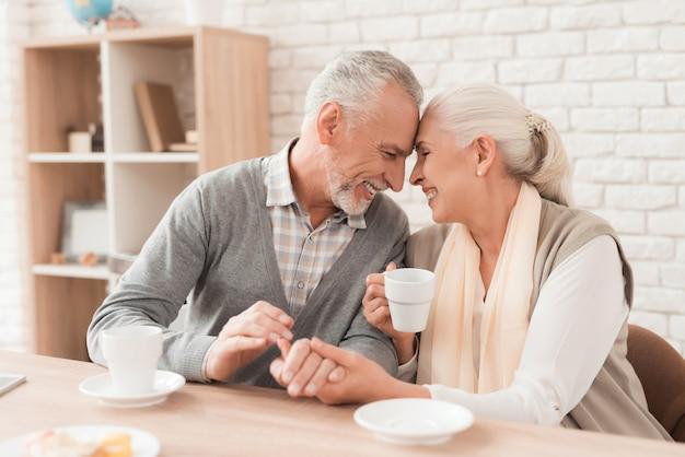 Couple de personnes âgées buvant du café en se tenant la main.