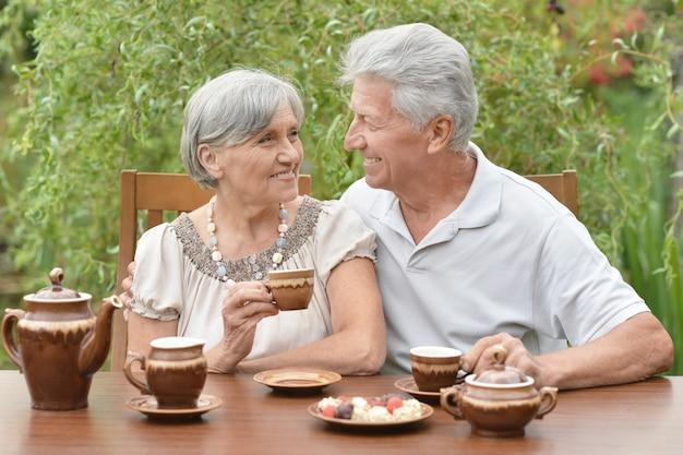 Couple de personnes âgées buvant du thé dans le jardin d'été