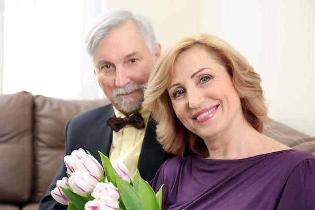 Couple de personnes âgées célébrant l'anniversaire de mariage à la maison
