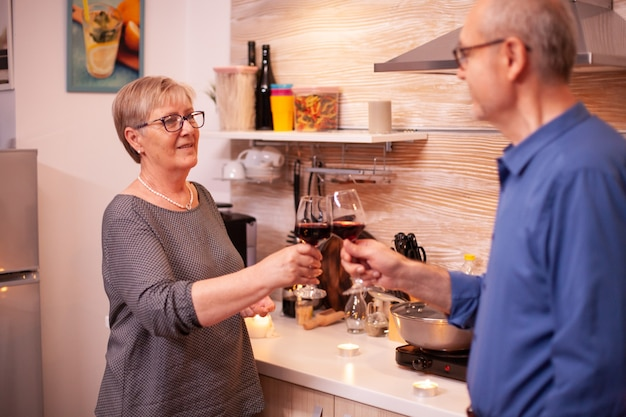 Couple de personnes âgées célébrant l'anniversaire de la relation avec du vin rouge. couple âgé amoureux de parler d'avoir une conversation agréable pendant un repas sain.