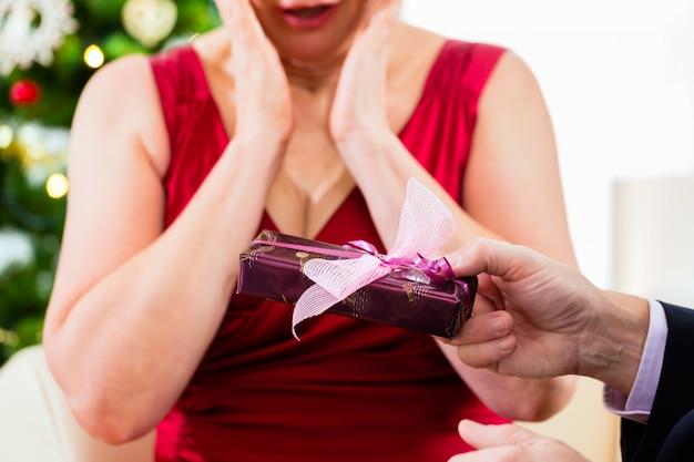 Couple de personnes âgées célébrant la veille de noël avec des cadeaux